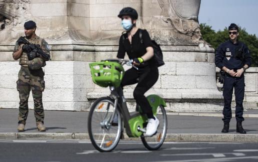 Un ciclista que usa una máscara facial pasa a un soldado francés y un oficial de policía en París.