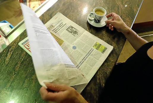 Una lectora hojea un ejemplar de 'Ultima Hora'.