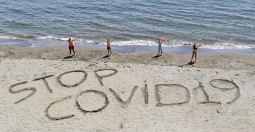Una familia ha escrito la frase 'Stop COVID-19' en la playa de Posillipo, cerca de Nápoles.