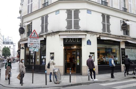 Gente haciendo cola en una tienda en París.
