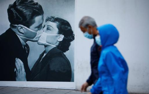 Una pareja pasea en España, haciendo uso de mascarillas.