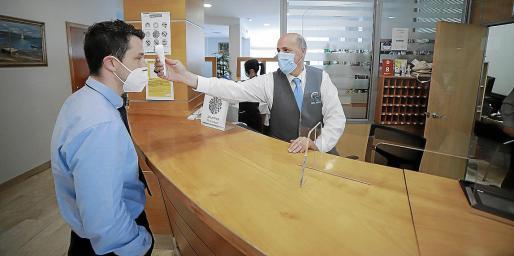 Sergio Alonso, director del hotel Abelux de Palma, se somete al control sanitario de temperatura.