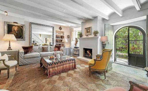 El salón presidido por la chimenea, con acceso al patio, destaca por su amplitud y luminosidad, y las vigas de madera.