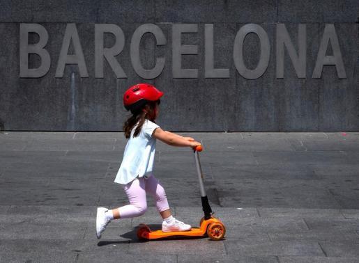 Una niña pasea con su patinete en Barcelona.