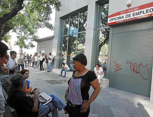 La gente hace cola a la espera de que abra una oficina de empleo en Madrid.