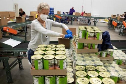 Voluntarios empaquetan alimentos para los más necesitados.