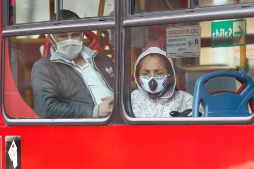 Personas con mascarillas se movilizan en un bus de transporte público en Bogotá (Colombia).