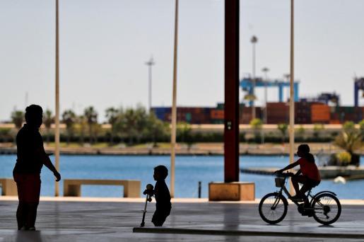 Un niño juega con su patinete mientras una niña pasea con su bicicleta ante la mirada de un adulto en La Marina de Valencia.