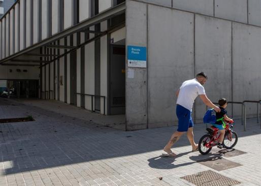 Un padre y su hijo pasean frente a una escuela cerrada en el barrio del Poble Nou de Barcelona.