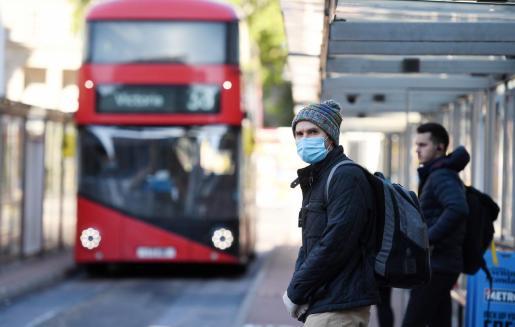 Gente con mascarilla en una parada de bus en Londres.