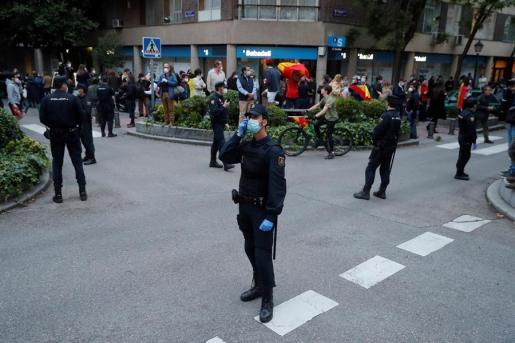 Vecinos del madrileño barrio de Salamanca se manifiestan contra el Gobierno, vigilados por un fuerte dispositivo policial, por su gestión en la crisis del coronavirus, este jueves en Madrid.