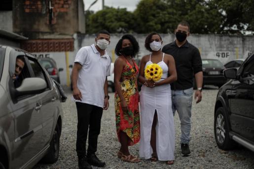 Mylena da Silva y Jhonatas Moreira dos Santos, posan con amigos para las fotografía, con mascarillas, antes de la boda dentro de un coche en plena pandemia, en Río de Janeiro.