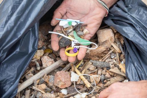 Una persona sostiene algunos de los plásticos encontrados en una playa de Menorca.