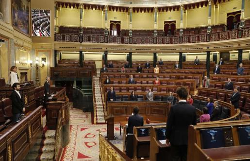 Los diputados guardan un minuto de silencio por las víctimas del coronavirus durante la sesión de control al ejecutivo en el Congreso en Madrid.