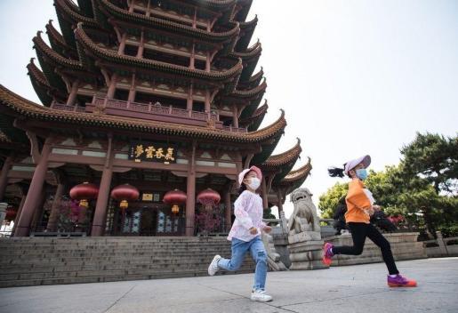 Dos niñas juegan en Wuhan, ciudad china donde comenzó el brote.