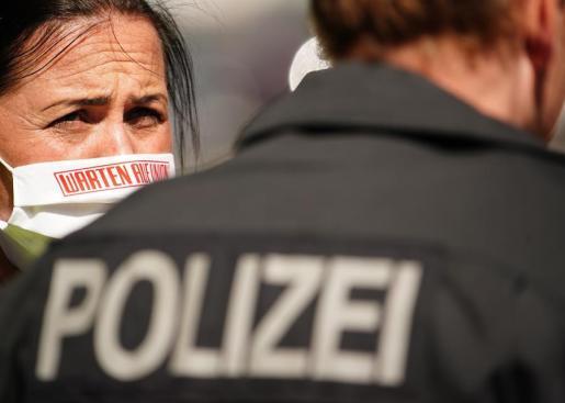 Una ciudadana con mascarilla, junto a un policía en Alemania.