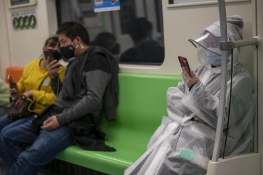 Varios pasajeros viajan en el metro, en China.