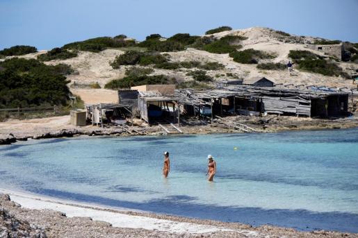 Dos personas se bañan en la playa de ses Illetes.