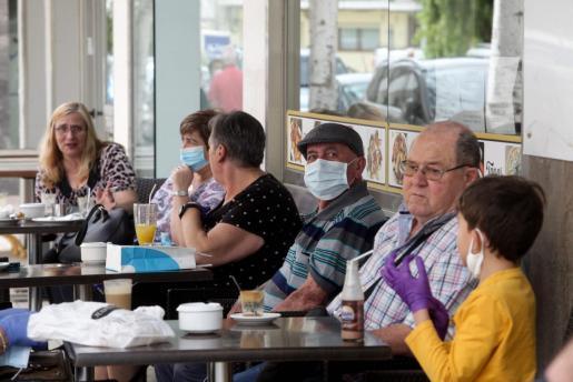 Gente con y sin mascarillas en la terraza de un bar.