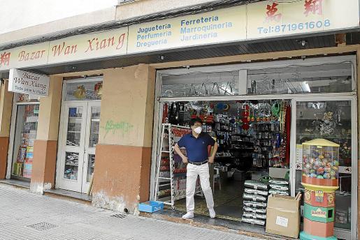 El encargado de un bazar espera clientela en su puerta.