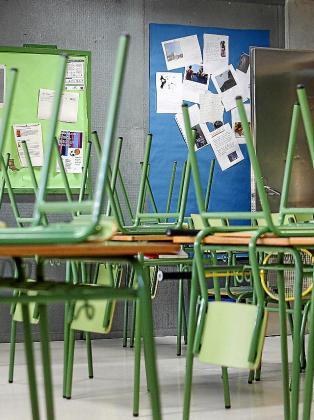 Mesas y sillas ordenadas en un aula vacía.