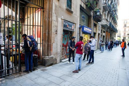 Ciudadanos, en Barcelona, hacen cola para recibir comida durante el estado de alarma por el coronavirus.