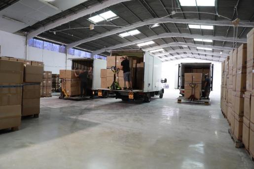 Los operarios colocan el material sanitario en uno de los almacenes donde hacen acopio.