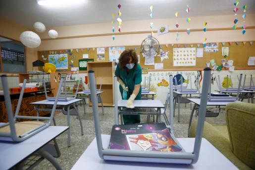 Una limpiadora desinfecta el mobiliario de un colegio.