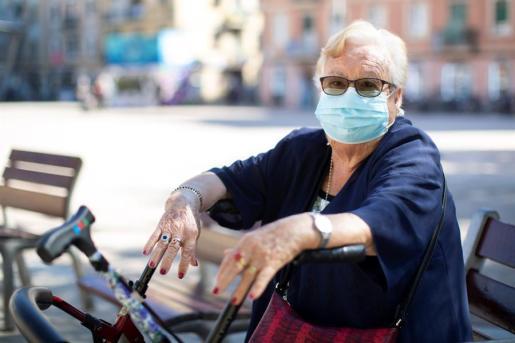Una mujer, en la calle, usa la mascarillas como protección frente al virus.