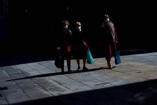 Tres personas mayores pasean por la calle con su mascarilla de protección.