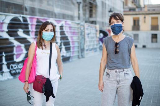 Mercè (i), de 50 años, y Núria (d), de 43, llevan unas mascarillas de tela sin filtro elaboradas por internos de prisiones.