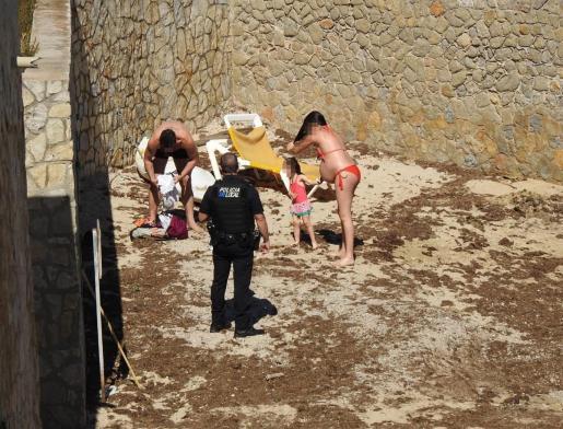Un agente de la Policía Local de Andratx con varios de los bañistas.