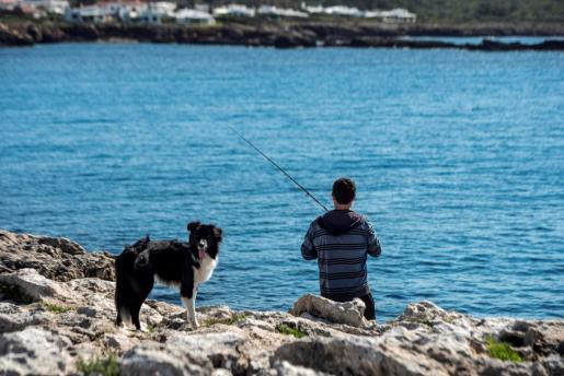 Un hombre pesca en en Cap d'en Font (Menorca). El Gobierno ha permitido finalmente la práctica de la pesca deportiva y recreativa, en los territorios que ya se encuentren en la fase 1 de la desescalada.
