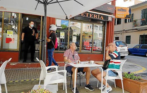 Un funcionario municipal (con casco) explica a Mariano Pérez, propietario del bar Tiqui, la nueva normativa.