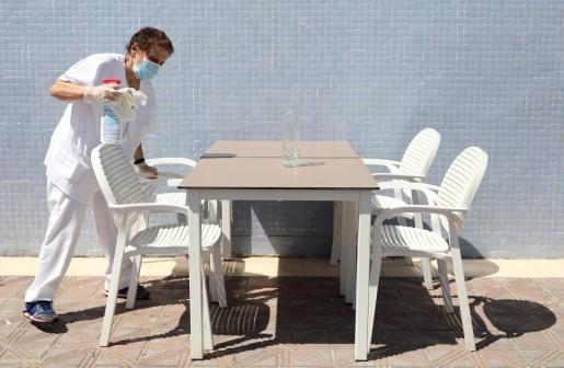 Una mujer desinfectando unas mesas y sillas en un establecimiento en Valencia.