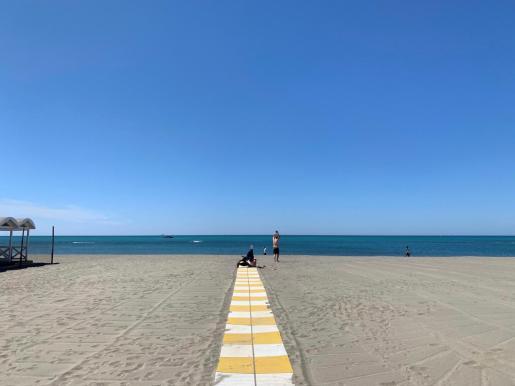 Un par de personas disfrutan de una playa.