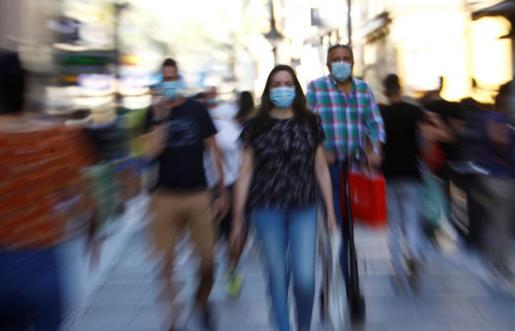 Ciudadanos protegidos con mascarillas pasean por el centro de Córdoba.
