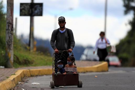 Un ciudadano venezolano y dos niños caminan por la carretera en Ecuador.