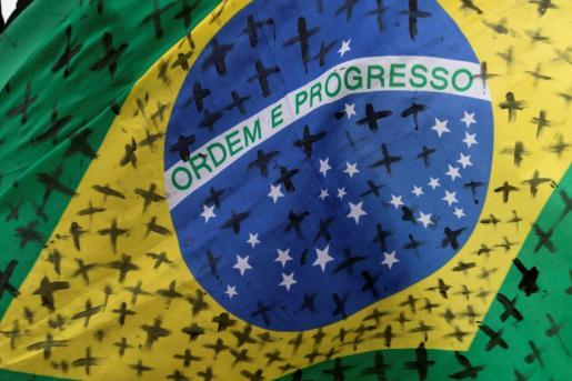 Detalle de la bandera de Brasil con cruces negras pintadas por las víctimas de la COVID-19 en ese país.