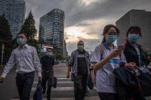 Varias personas circulas con mascarillas por las calles de Beijing.