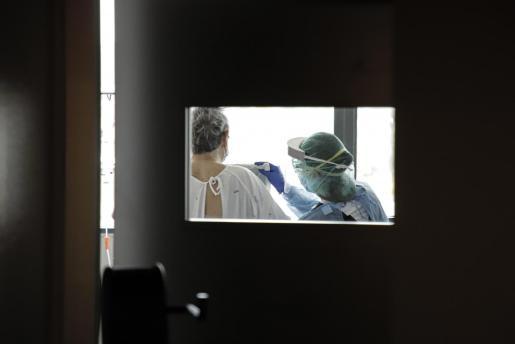 Un sanitario, junto a un paciente en el hospital Son Espases.
