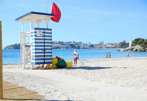 La playa de es Carregador con bandera roja.