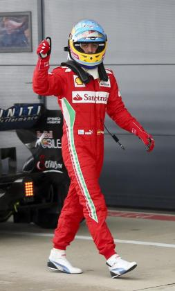 El piloto español de Fórmula Uno, Fernando Alonso de Ferrari saluda al público tras conseguir la pole.