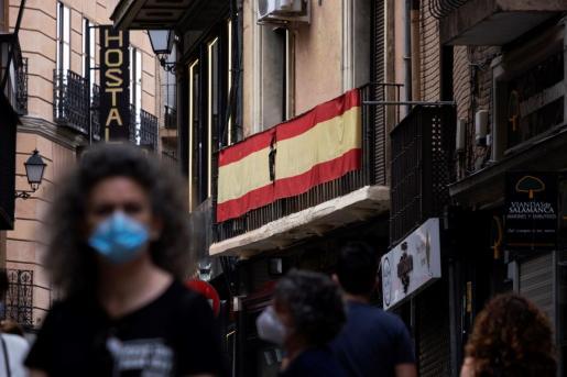 Una bandera luce un crespón negro con motivo del luto nacional por las víctimas del coronavirus.