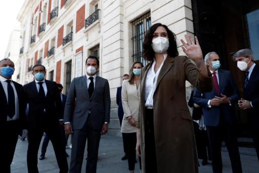 La presidenta de la Comunidad de Madrid, Isabel Díaz Ayuso, saluda a los ciudadanos antes de participar en el minuto de silencio en memoria de los fallecidos por el COVID-19.
