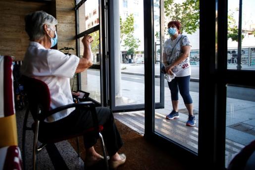 Esther, visita a su madre Irene en la residencia geriátrica Icaria, del Barrio de Poble Nou de Barcelona a través de la puerta siguiendo las medidas de seguridad de la Fase 1 de desescalada.