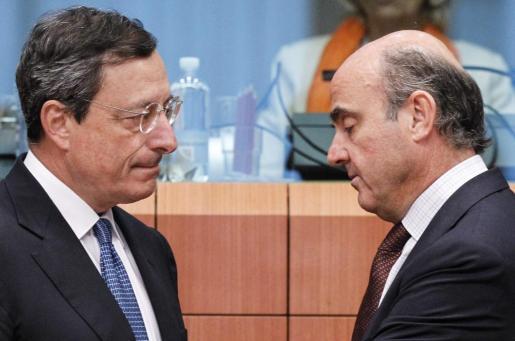 El presidente del Banco Central Europeo (BCE), Mario Draghi (i), y el ministro español de Economía y Competitividad, Luis de Guindos (d), conversan durante la reunión de los ministros de Finanzas de la UE.
