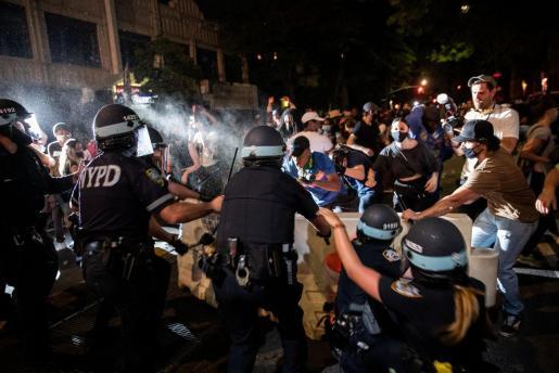 Un oficial de policía rocía a los manifestantes durante una marcha contra la muerte en Minneapolis de George Floyd, en el distrito de Brooklyn de la ciudad de Nueva York.