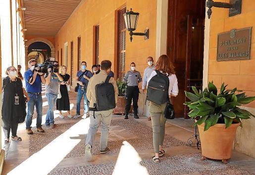 Representantes de los medios en la puerta del Parlament mientras entran un diputado y una diputada.