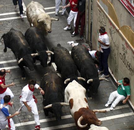 Varios mozos pasan apuros ante los toros de la ganadería de Fuente Ymbro, a su paso por la calle de la Estafeta, durante el quinto encierro de los sanfermines 2012.